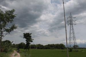 Tiang bambu yang menopang kabel listrik dari meteran resmi PLN dan menara SUTET di sepanjang jalan menuju Dukuh Santren. Di kejauhan Dukuh Santren. Foto: Rusdi Mathari