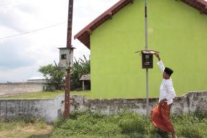 Danang Sutrisno menunjukkan dua meteran resmi PLN di seberang pagar tembok SDN 03 Tiron. Dari dua meteran itulah, warga Santren menarik kabel ke rumah-rumah mereka karena PLN tak bersedia. Foto: Rusdi Mathari